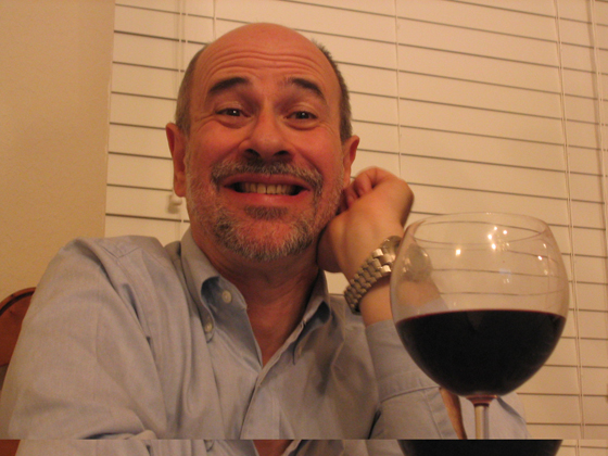 John smiling with glass of wine in foreground